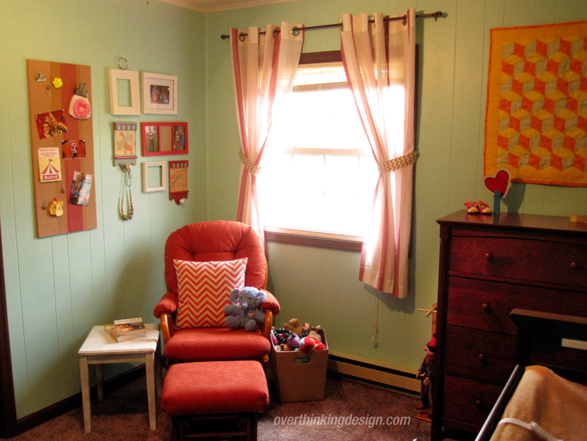 A bright orange rocking chair takes center stage in one corner of the circus-themed baby room